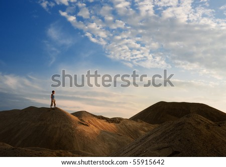 young man go up in sand desert in sundown silhouette