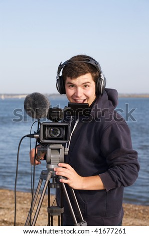 Young man grinning as he films you - stock photo