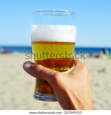 young man hand holding a refreshing beer on the beach - stock photo