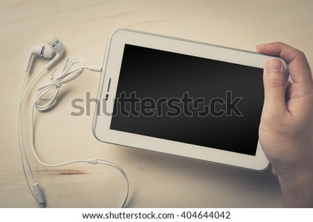 Young man hand holding small tablet pc screen on wood table with in ear headset beside with vintage filter effect - stock photo