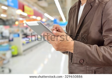 Young Man Hands holding Tablet or Mobile Device in Supermarket or Hypermarket store as Digital environment Working. Selective Focus on Right Pointer Finger or Trigger Finger. - stock photo