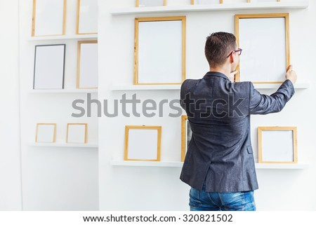 young man hanging a blank white frames in exhibition hall - stock photo