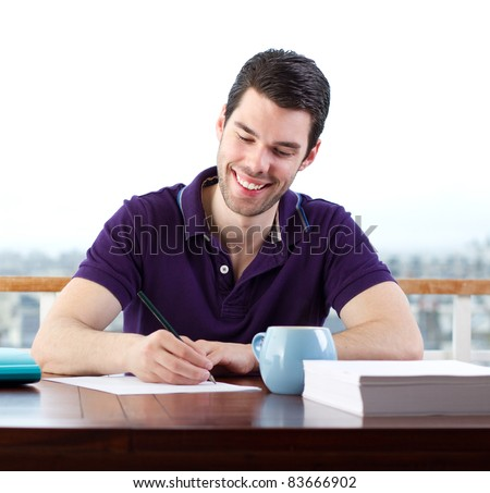 Young man happily writing a letter by hand - stock photo