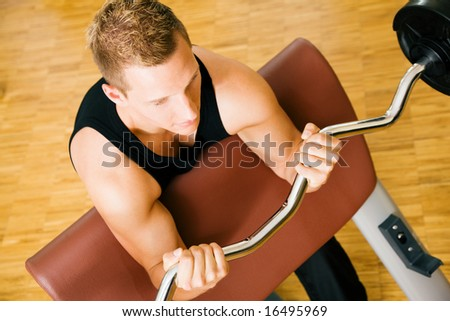 Young man having a training session in the gym using a barbell - stock photo