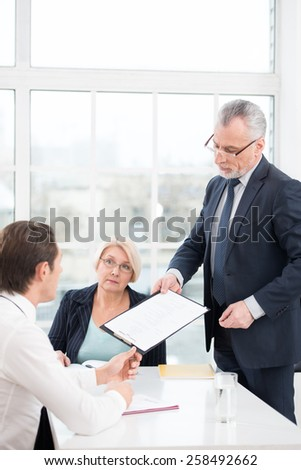 Young man having an interview or business meeting with employers. Director giving prospective employee to complete a questionnaire. Office interior with big window - stock photo