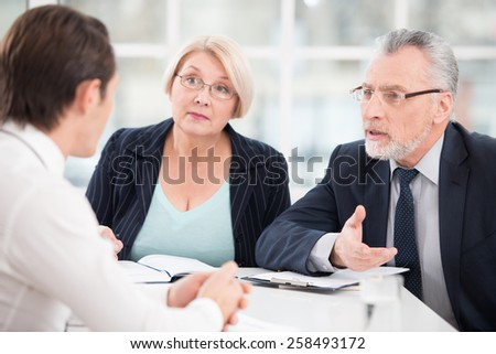 Young man having an interview or business meeting with employers. Office interior with big window - stock photo