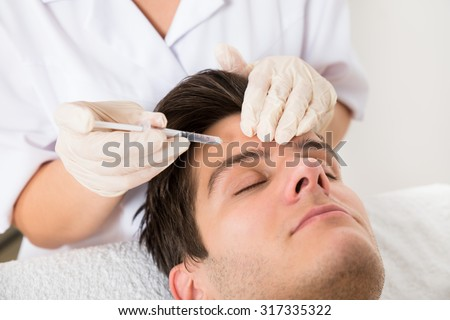 Young Man Having Botox Treatment At Beauty Clinic - stock photo
