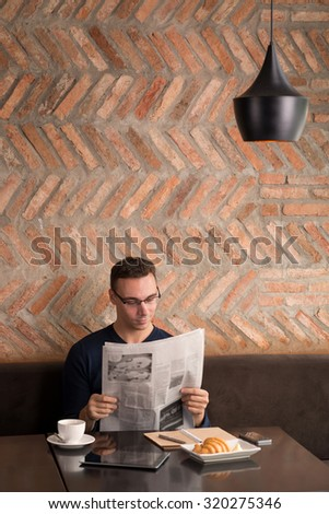 Young man having breakfast and reading newspaper in a cafe - stock photo