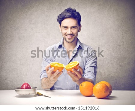 young man having breakfast with oranges - stock photo