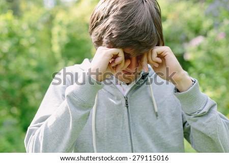 Young man having eye pain and rubbing his eyes - stock photo