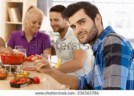 Young man having fondue party with friends, holding dipping stick, smiling, looking at camera. - stock photo