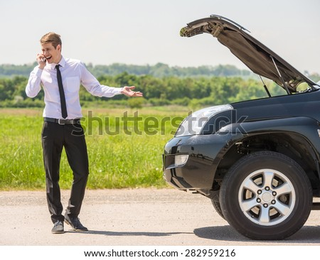 Young man having trouble with his broken car, opening hood and calling for help on cell phone. - stock photo