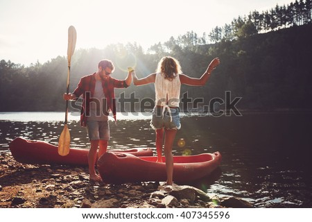 Young man helping woman to step into the kayak. Couple going for a canoe ride in the lake. - stock photo
