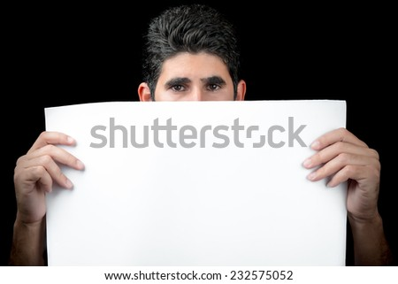 Young man hiding behind a white banner with space for text (isolated on black) - stock photo