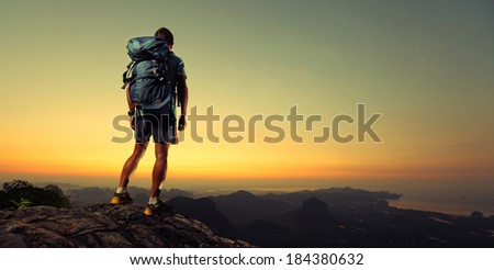 Young man hiker standing on top of the mountain completed his trek at sunrise - stock photo