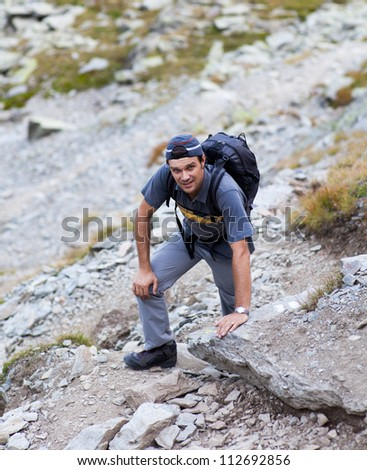 Young man hiking on mountain trail - stock photo