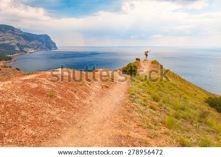 Young man hiking on the cliff above the sea