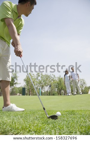 Young man hitting ball on the golf course - stock photo