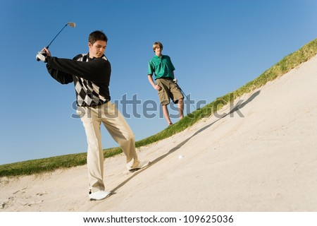 Young man hitting golf ball out of a sand trap - stock photo