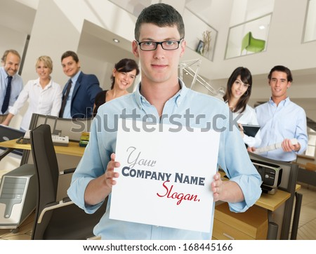 Young man holding a blank sign in an office with a supporting team