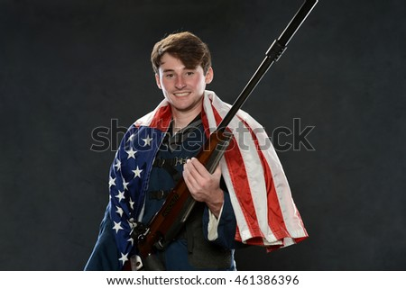 Young Man holding a gun with American flag isolated on a gray background