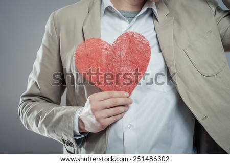 young man holding a heart in his hands - stock photo