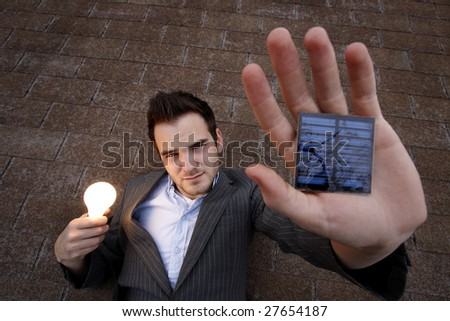 young man holding a lightbulb and a solar panel. - stock photo