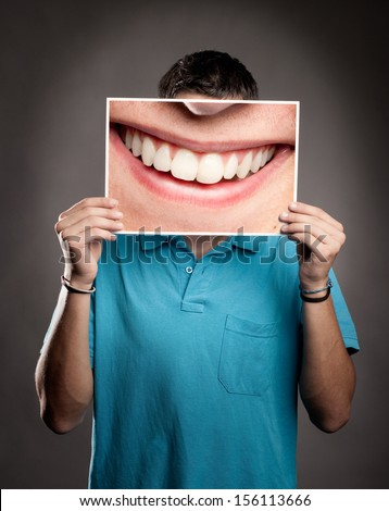 young man holding a picture of a mouth smiling - stock photo
