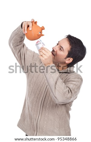 young man holding a piggy bank and putting euro bills inside it - stock photo