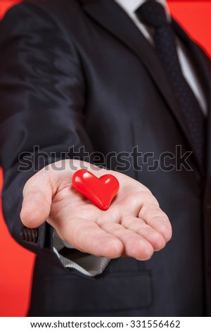 Young man holding a red heart on the palm, red background - stock photo