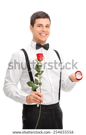 Young man holding a rose and an engagement ring isolated on white background