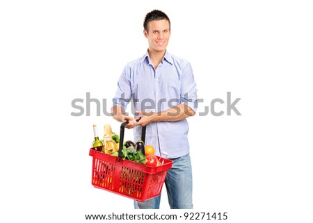 Young man holding a shopping basket full with products isolated against white background