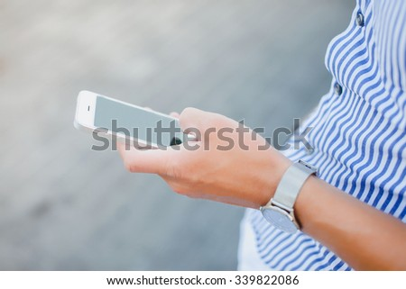 young man holding a smartphone on his  hand ,travel people,mans golden hand-watch,smartphone typing massages,tan man,working hard,using iphone and meeting friends  - stock photo