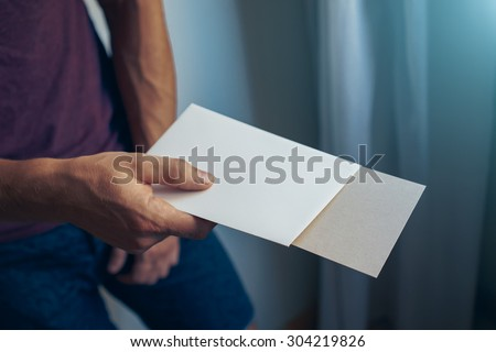 young man holding a white & brown blank envelopes