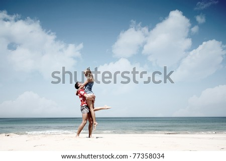 Young man holding a woman and standing on warm sand at sunny day by a sea - stock photo