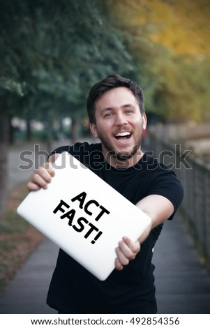 Young man holding Act Fast! sign
