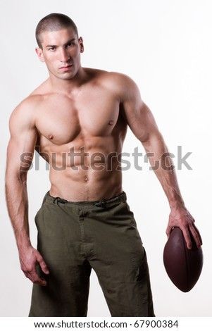 Young man holding american football ball - stock photo