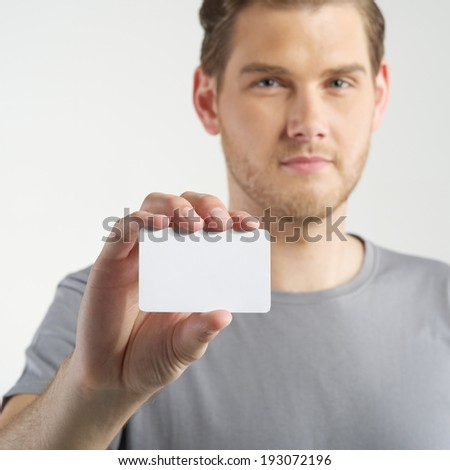 young man holding and showing blank card  - stock photo