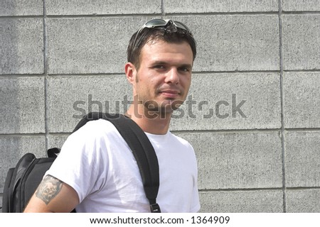 young man holding backpack - stock photo