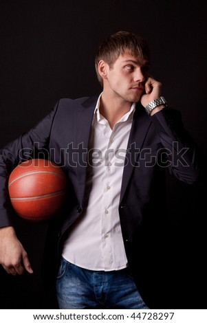 Young man holding basketball ball and celling by the phone - stock photo