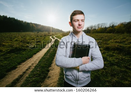 Young man holding Bible in a park - stock photo