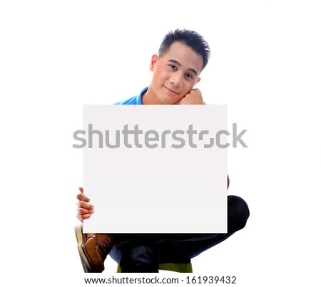 Young man holding blank billboard