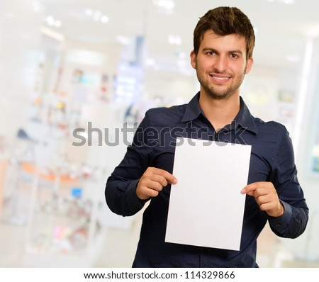 Young Man Holding Blank Paper, Indoors - stock photo