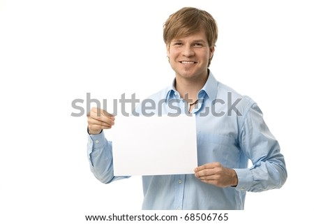 Young man holding blank sheet of paper, smiling. Isolated on white.
