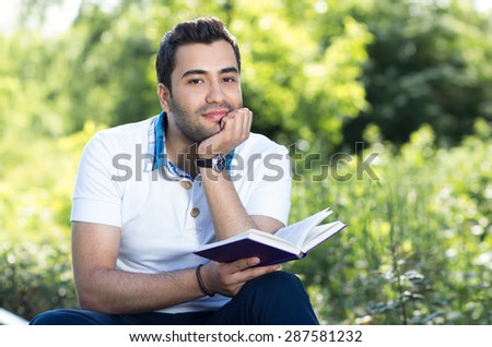 Young man holding book and sittingin a forest. outside - stock photo