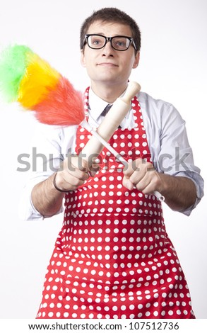Young man holding duster and kitchen tool. - stock photo