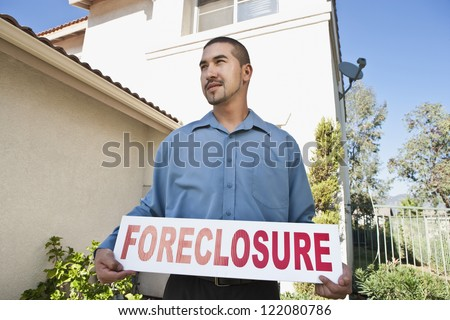 Young man holding 'Foreclosure sign' with house in the background - stock photo