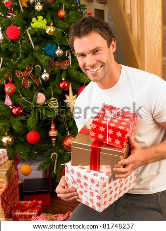 Young man holding gifts in front of Christmas tree - stock photo