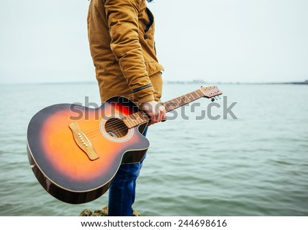 young man holding guitar at the lake - stock photo