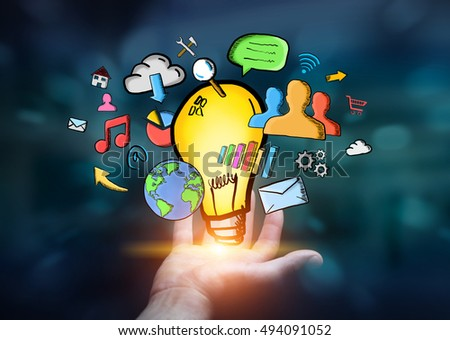 Young man holding hand drawn lightbulb in his hand with multimedia icons flying around